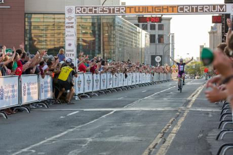 racers cross the finish line in the Rochester Criterium