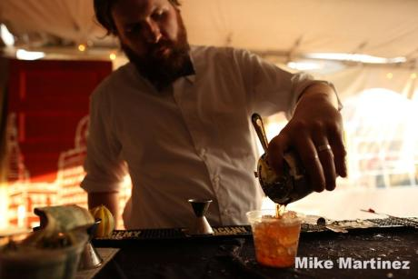 Bartender pours a drink over ice at the Rochester Cocktail Revival