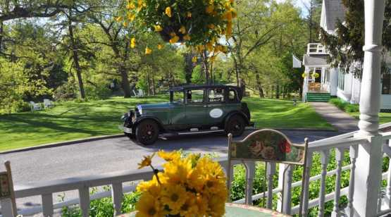 AWI classic car parked in front of porch