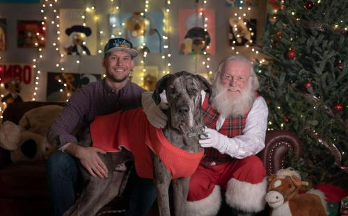 Santa, a great dane and the dog's owner posing for a photo.