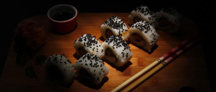 Sushi roll with black sesame seeds on wood serving tray