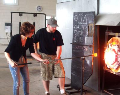 Instructor teaching student glass blowing in the furnace at Glass Axis