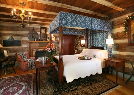 Four poster bed with blue hangings, white cover and oriental rugs on the hardwood floor.
