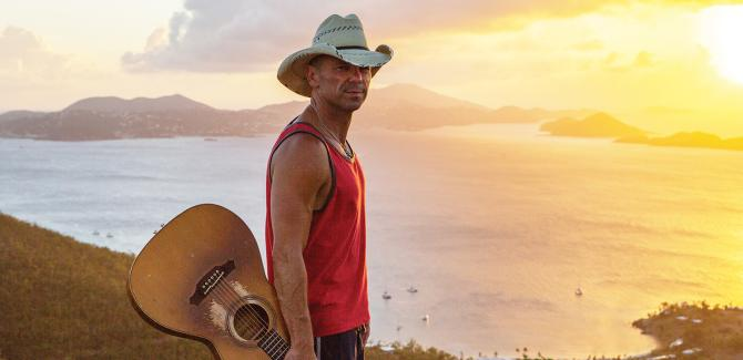 Country music artist Kenny Chesney holds his guitar and stands on a beach while the sun sets behind him