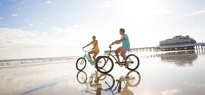A couple enjoys bicycling on Daytona Beach near the Main Street Pier