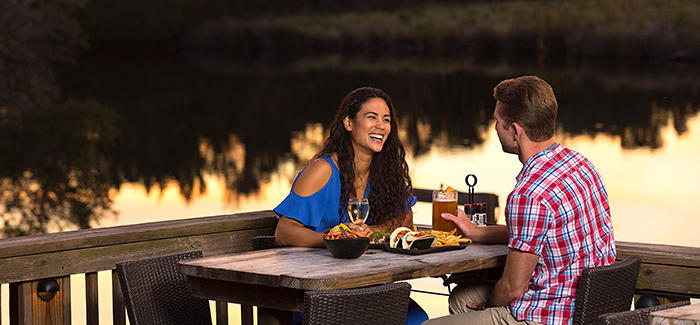 A couple enjoys a meal dining on the riverfront