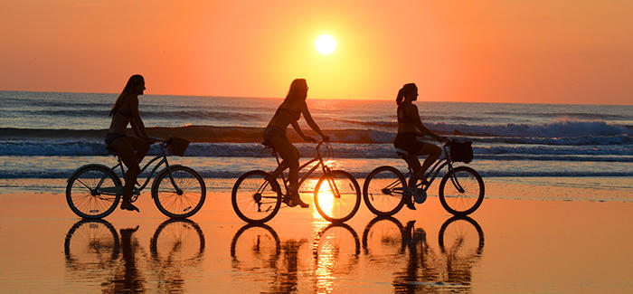 Three women enjoy a sunrise bicycle ride on Daytona Beach.