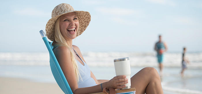A woman enjoys a cup of coffee while sitting at the beach.