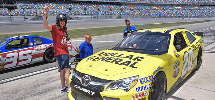 People are gathered around a stock car at Daytona International Speedway and are about to experience the NASCAR Racing Experience.
