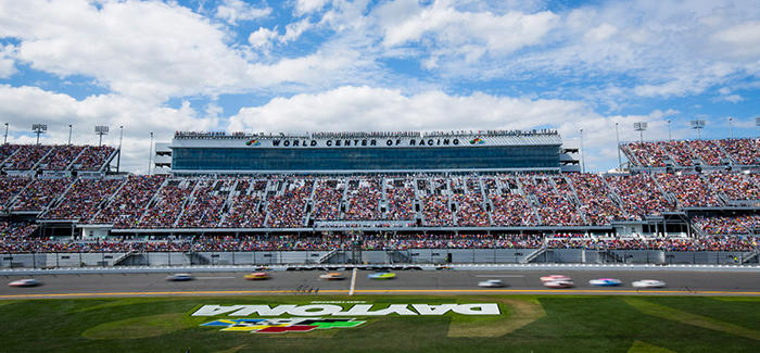 A view of Daytona International Speedway from the infield with sunny blue skies and cars racing around the track.