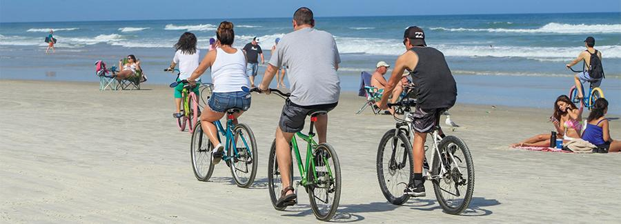 With plenty of elbow room, a family easily bicycles along the hard packed sands of Daytona Beach