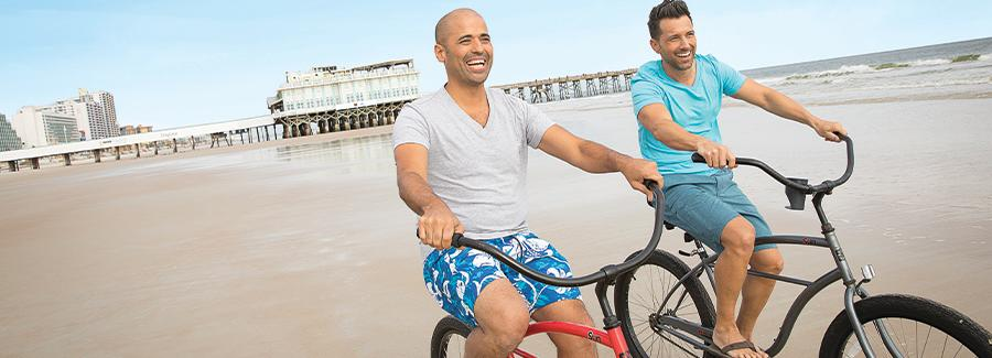 A couple of men enjoy a bicycle ride on the hard-packed sands of Daytona Beach