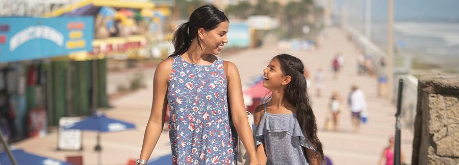A mother and daughter enjoy strolling along the Daytona Beach Boardwalk