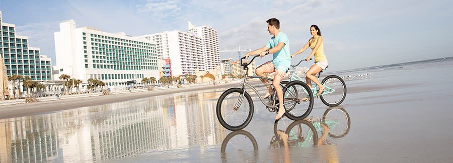 A couple enjoys bicycling on the hard-packed sands of Daytona Beach