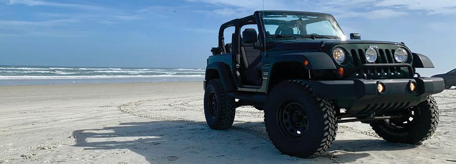 A jeep sits parked on the hard-packed white sands of Daytona Beach