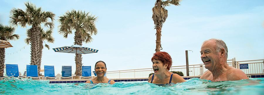 Friends enjoy a heated pool while on a Daytona Beach vacation