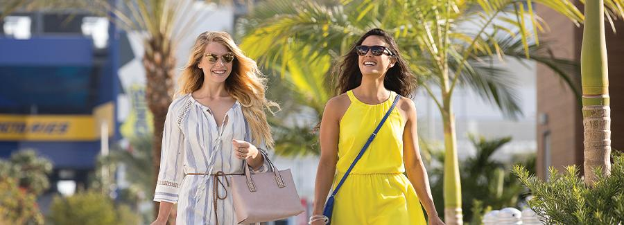 Two woman stroll while shopping at an outdoor outlet