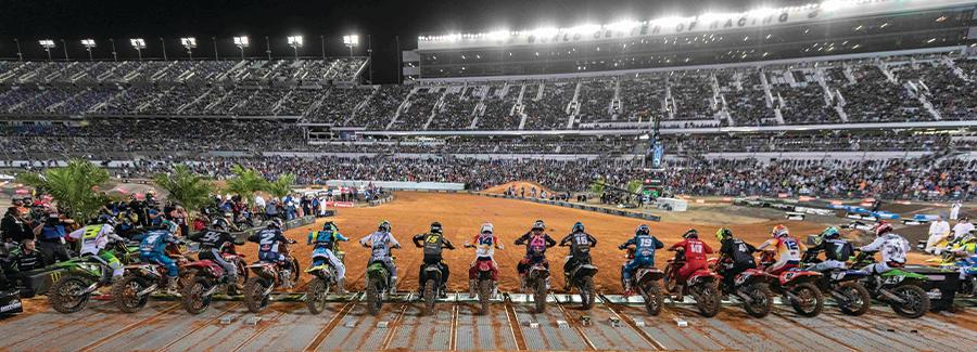 A line of motorcycle supercross racers is ready to compete under the lights at the World Center of Racing, Daytona International Speedway