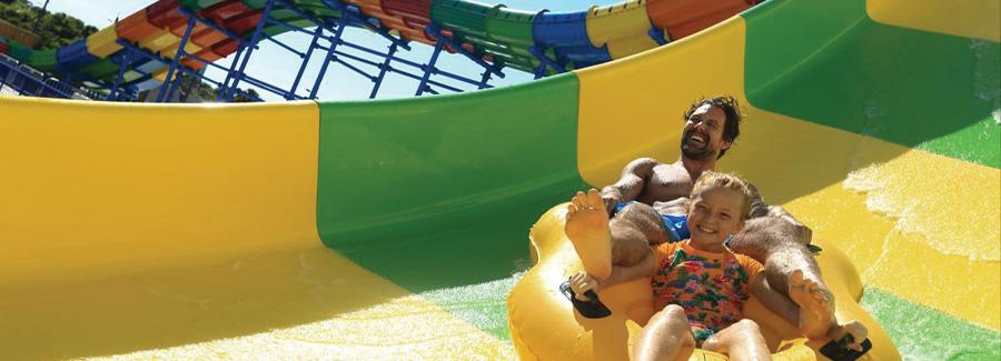 A father and daughter enjoy a fun water slide at Daytona Lagoon