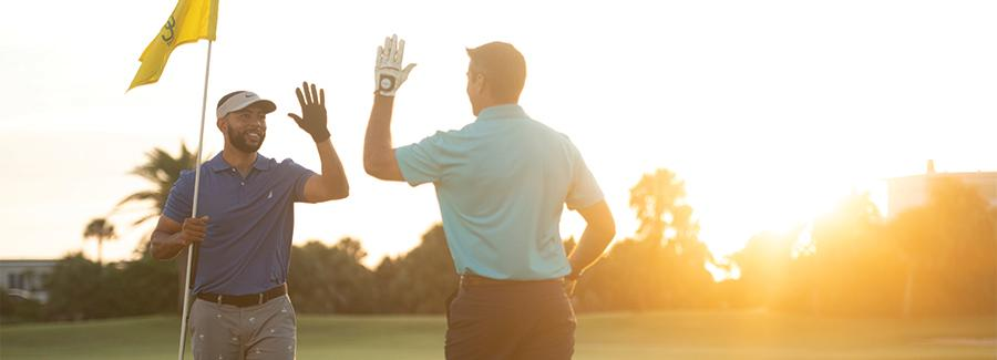 Golfers high five on the green at one of Daytona Beach's many great golf courses