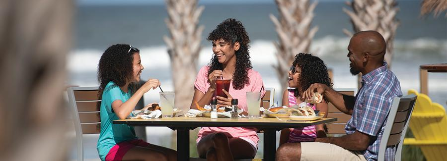 A family enjoys a meal together on the Daytona Beach oceanfront at Landshark Bar & Grill