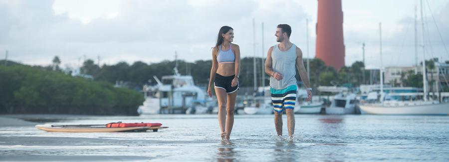 A couple strolls a sandbar after paddleboarding near Ponce Inlet Lighthouse