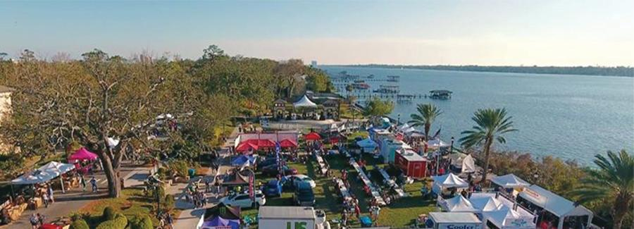An aerial view of a festival happening along the Halifax River at Rockefeller Gardens in Ormond Beach