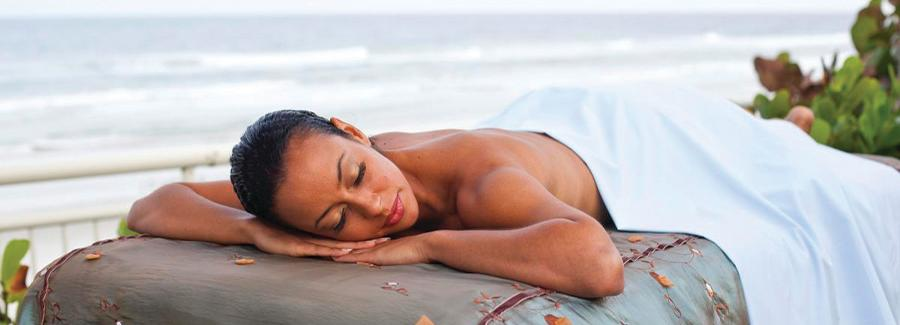 A visitor enjoys relaxing on the oceanfront after a spa treatment