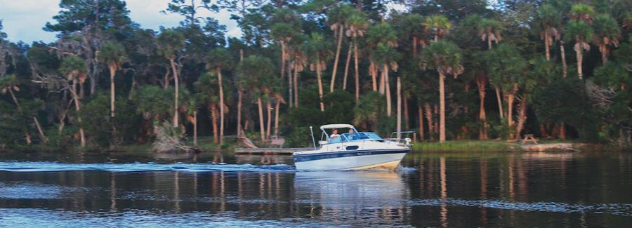 A fishing boat cruises along the Tomoka River