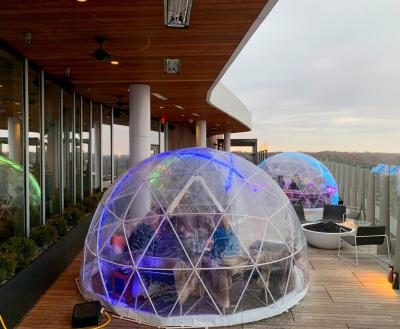People drinking and dining inside large plastic domes on Vaso Dublin's rooftop lounge