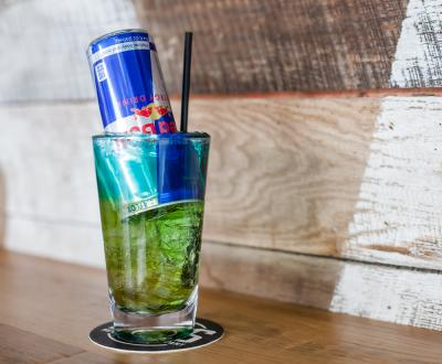 Green cocktail with red bull filled upside down in drink