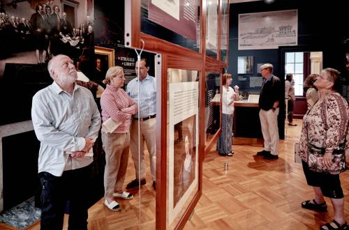 A group looking through an exhibit at morven museum