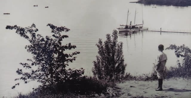 Historic photo of boy overlooking Saratoga Lake with boat in background