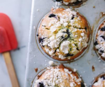 Tin of blueberry muffins topped with powdered sugar next to spatula at Cherbourg Bakery