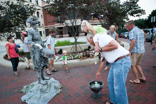 Man tipping Silver Lady statue street performer
