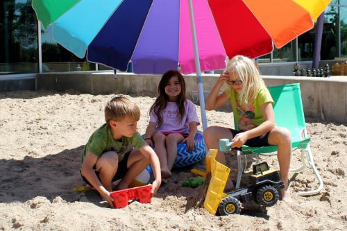 three children playing in sand under rainbow umbrella