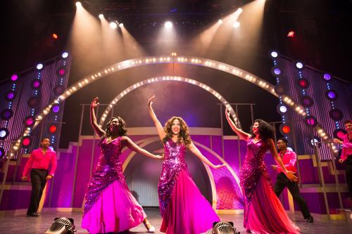 "Three women in pink glittering dresses on stage under bright lights in a Short North Stage production of ""Dreamgirls"""