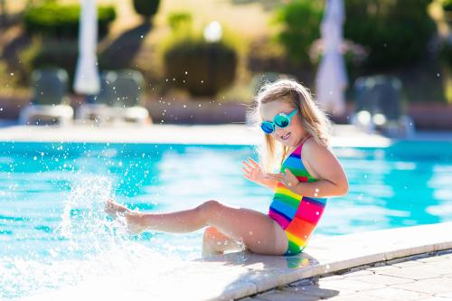 A child wearing a bright swimsuit splashes at the edge of a hotel pool.