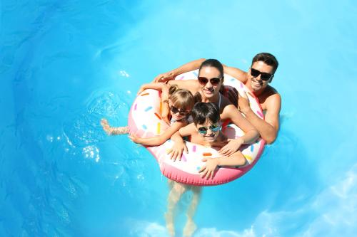 A family enjoys quality time together in the pool during their staycation in Irving, TX.
