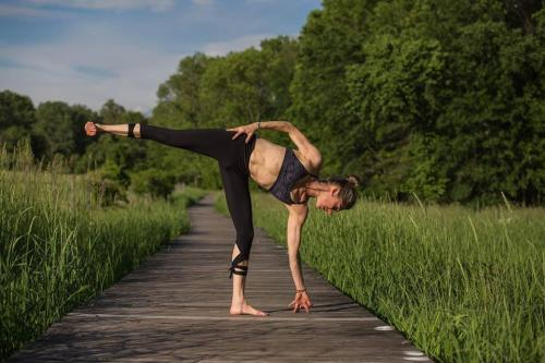 A woman doing yoga outside on a path