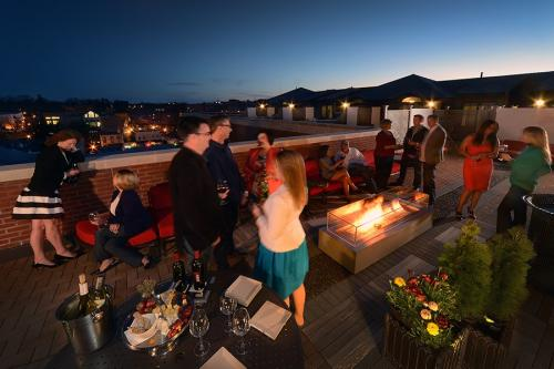 Group enjoying drinks and fire pit on the Pavilion Grand Hotel balcony in Saratoga Springs, NY at night
