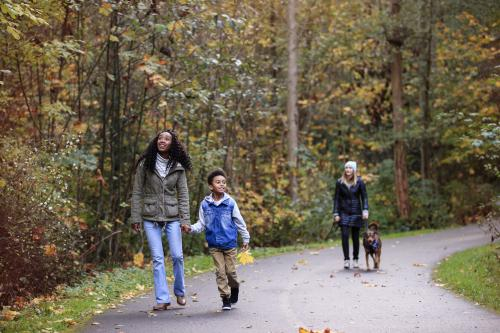 Mother and son walking trail and woman walking dog