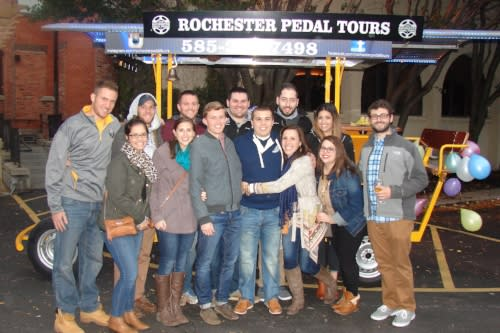 Group of people enjoy a pedal tour ride through Rochester, NY