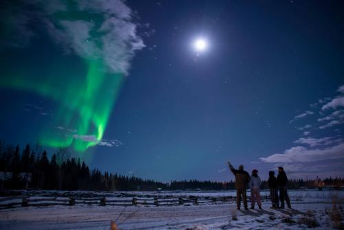 Aurora and full moon with four people watching