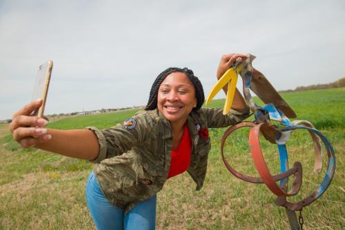 Teenager takes selfie with folk art near Lucas, Kansas