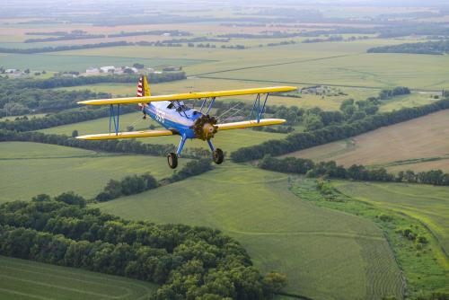 Blue and yellow plane flying over Kansas countryside