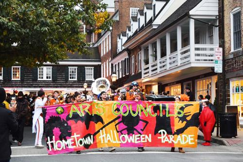 A banner at the start of a parade that reads arts council hometown Halloween parade