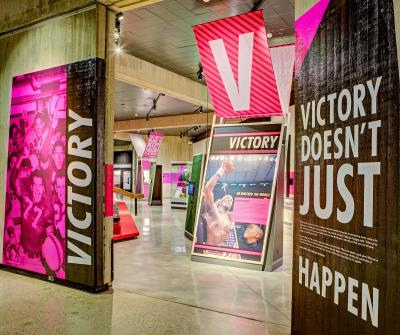 """Hot pink signage with black and white text, large-scale images in the """"Victory"""" section of """"Ohio - Champion of Sports"""" exhibit at Ohio History Center"""