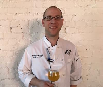 Wolf's Ridge Chef Seth Lassak in chef's coat holding beer from the brewery