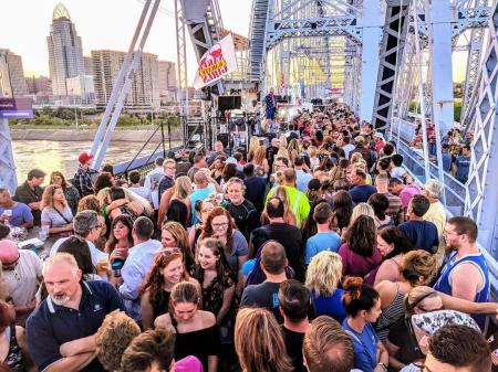 crowd of people and a band playing at party on the purple on the purple people bridge in newport ky and cincinnati oh